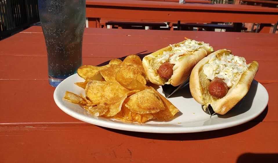 Two hot dogs topped with sauerkraut on a plate with potato chips and a glass of soda