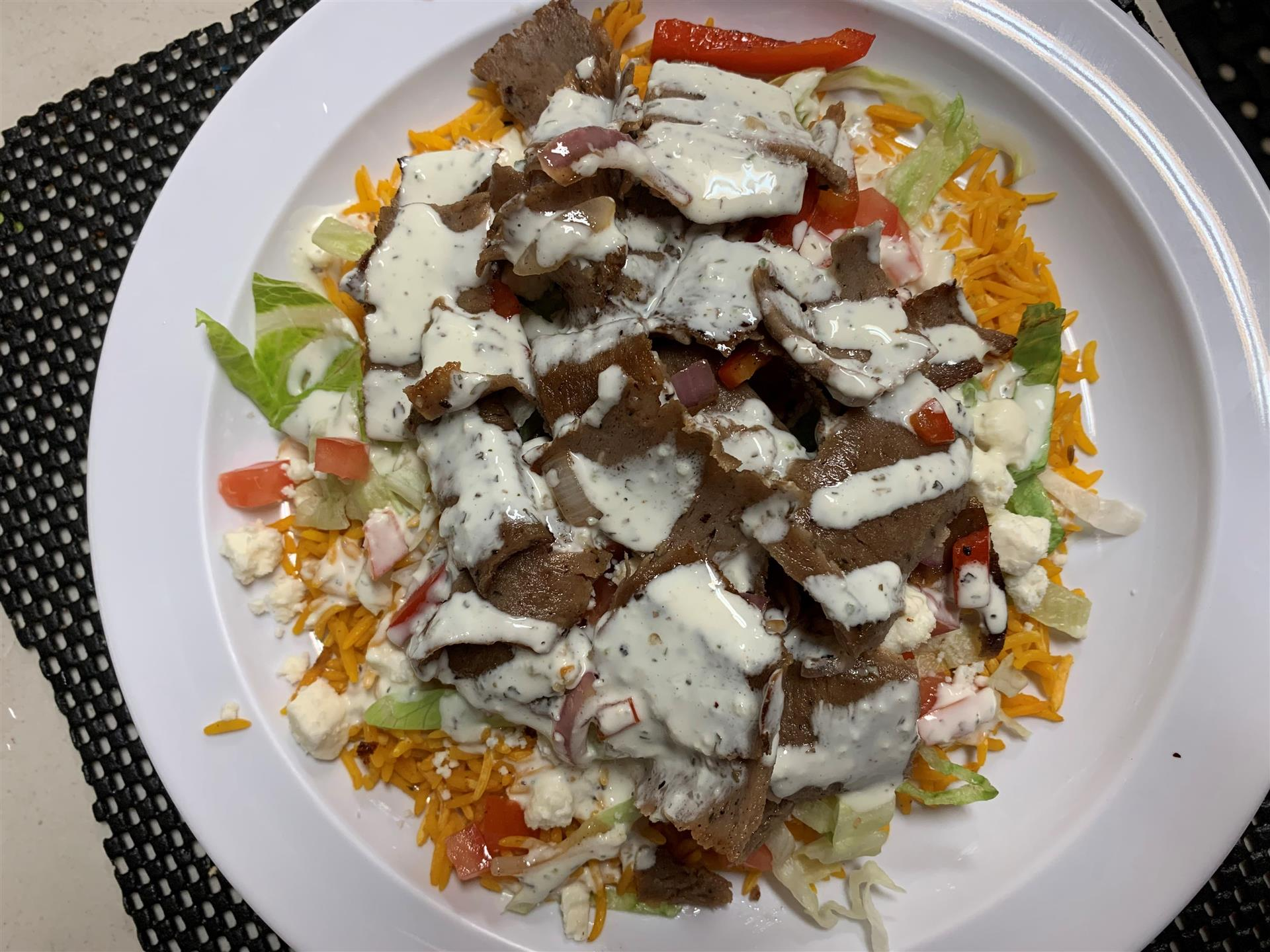 meat topped with Tzatziki sauce over a bed of lettuce, veggies and feta cheese