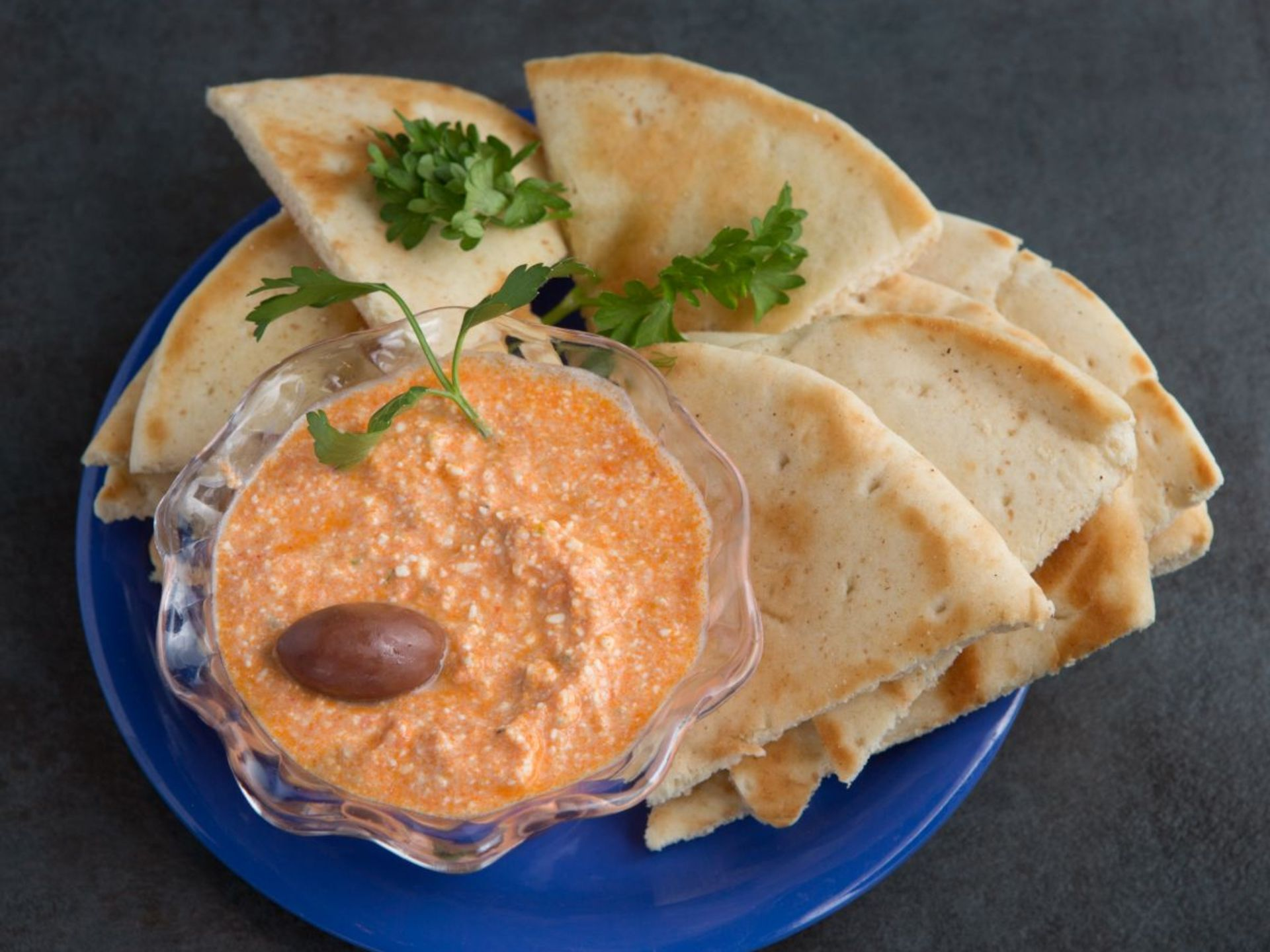 Pita bread on a plate with parsley and a small bowl of hummus