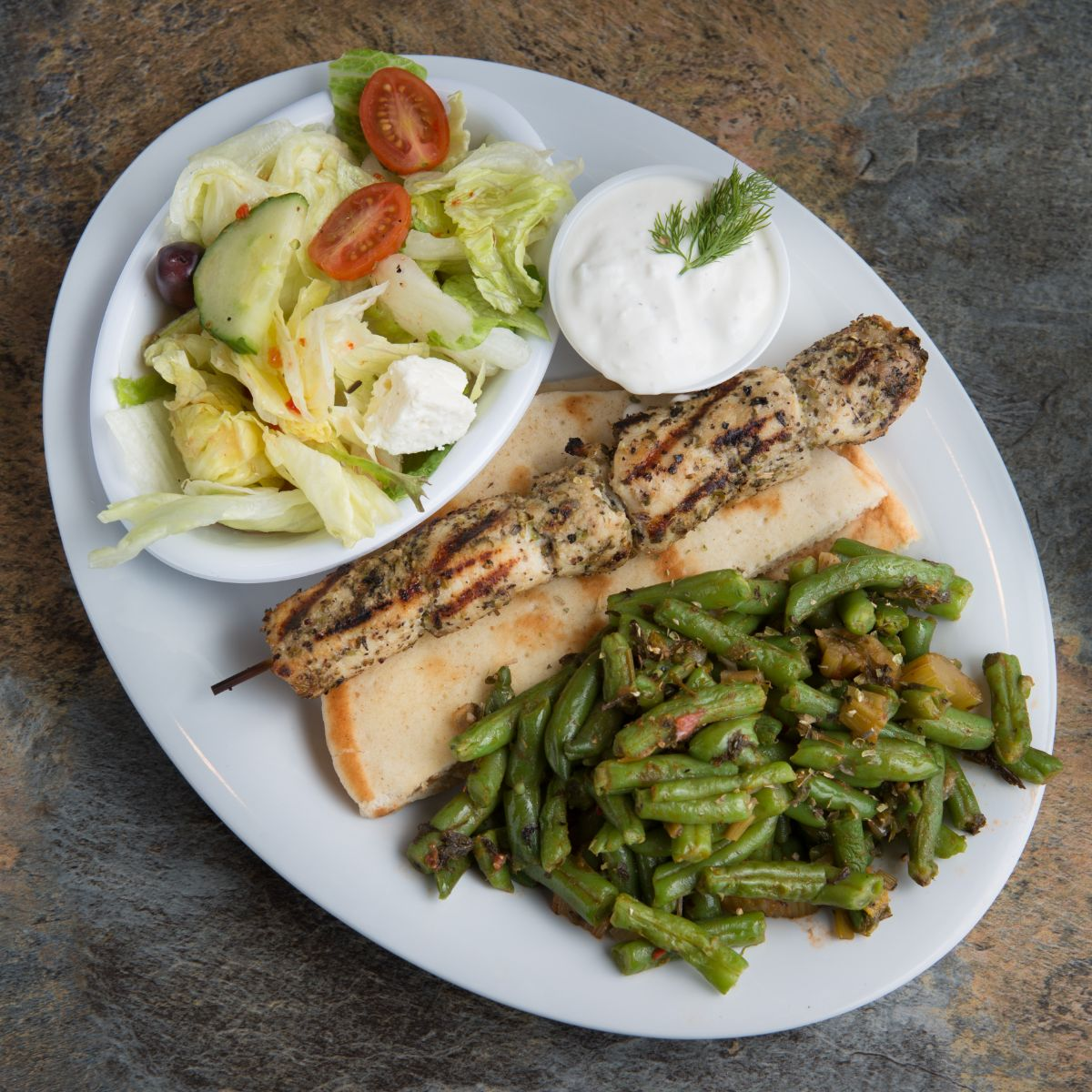 Chicken souvlaki with greek green beans, side salad and pita bread