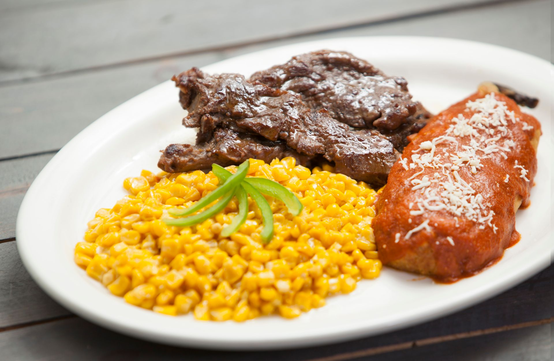 Skirt steak and enchilada with a side of corn