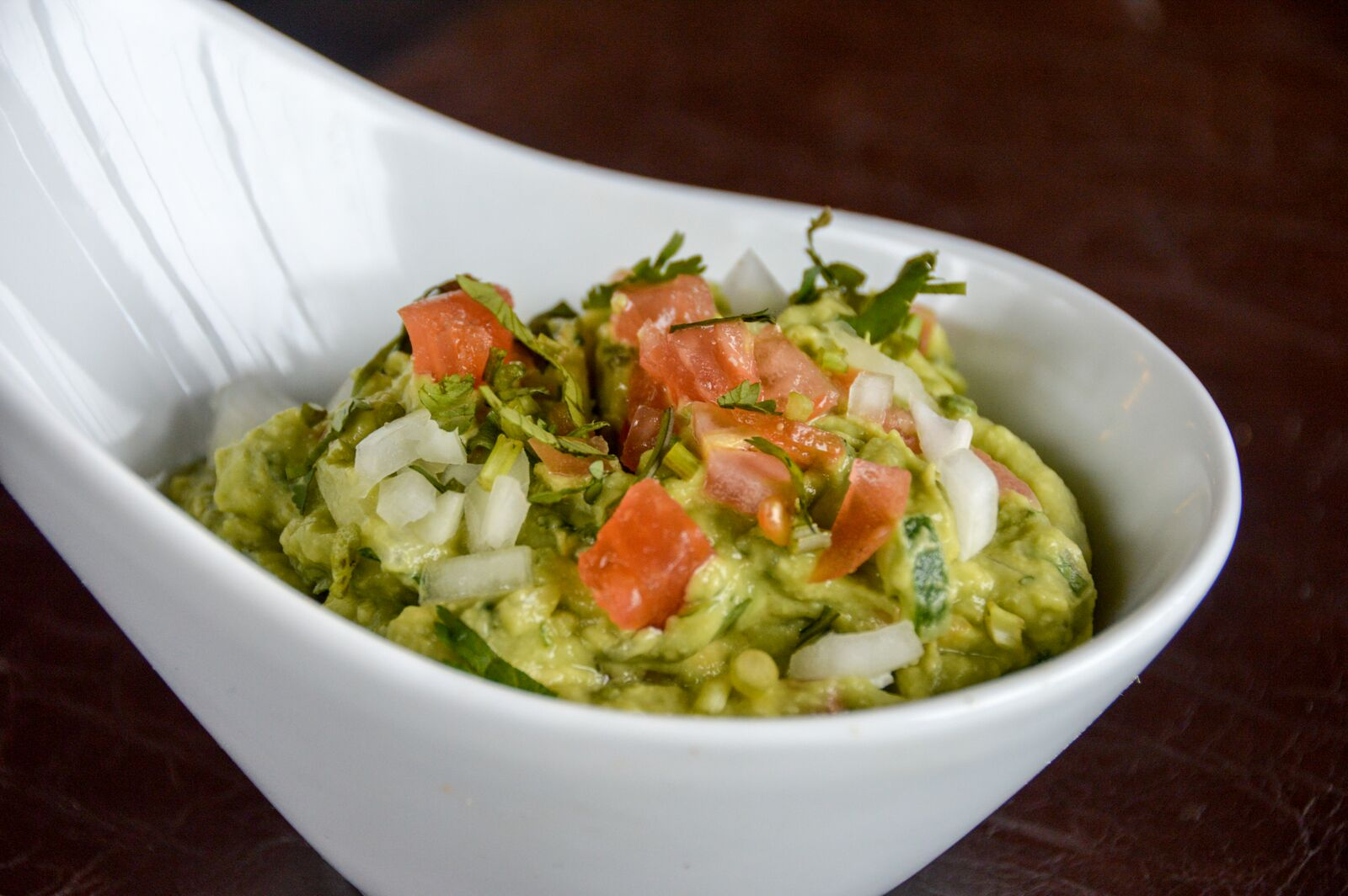 bowl of guacamole with tomatoes and onions