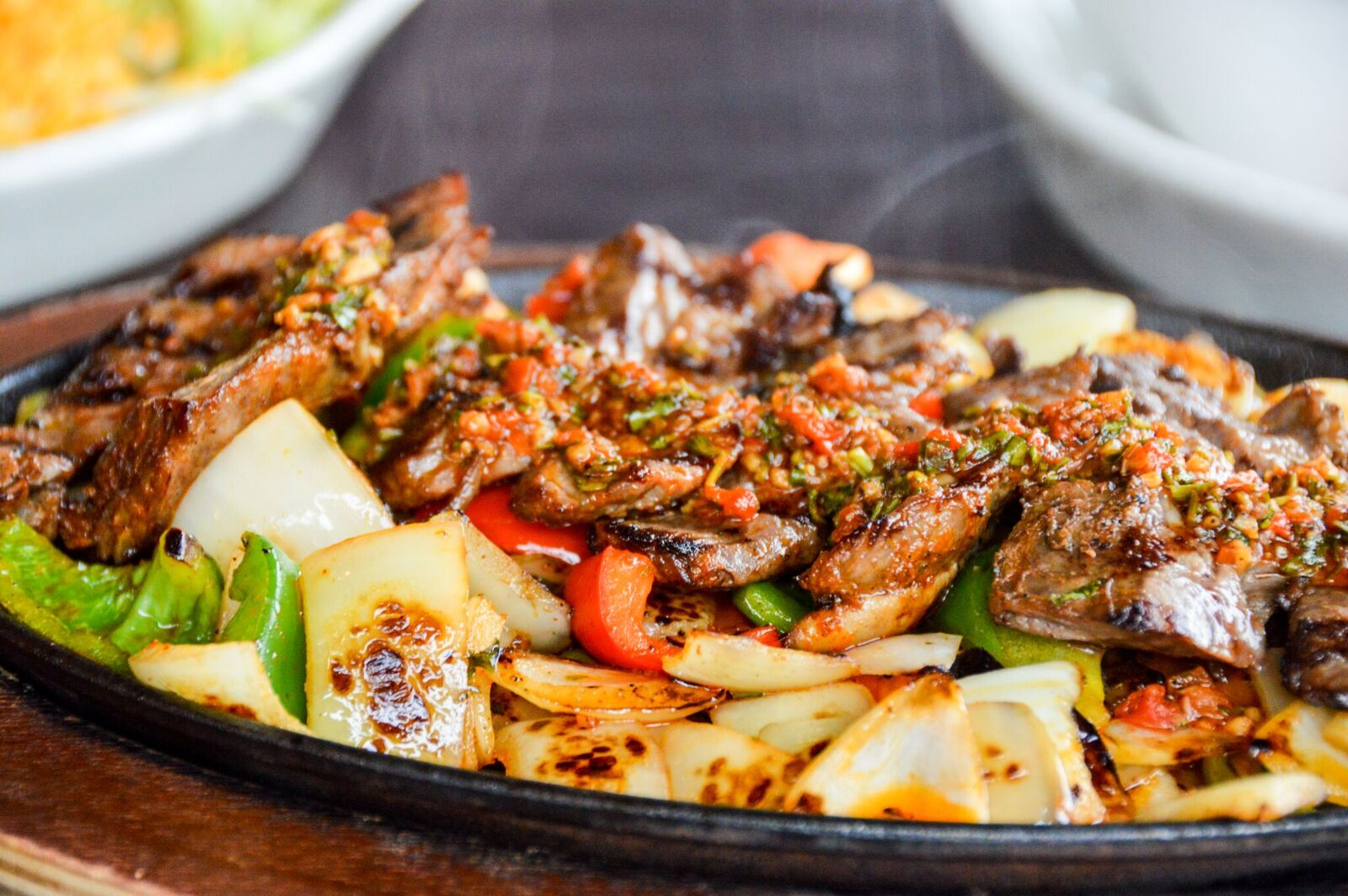 fajitas on a hot plate with steak, red peppers, green peppers and onions