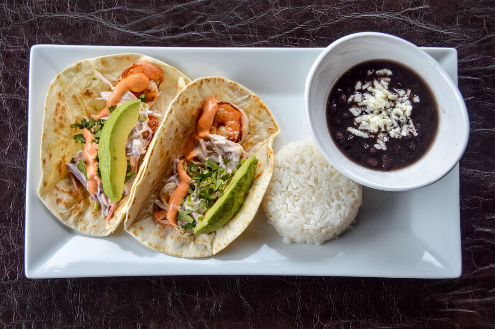 two tacos with shrimp and avocado with a side of rice and black beans