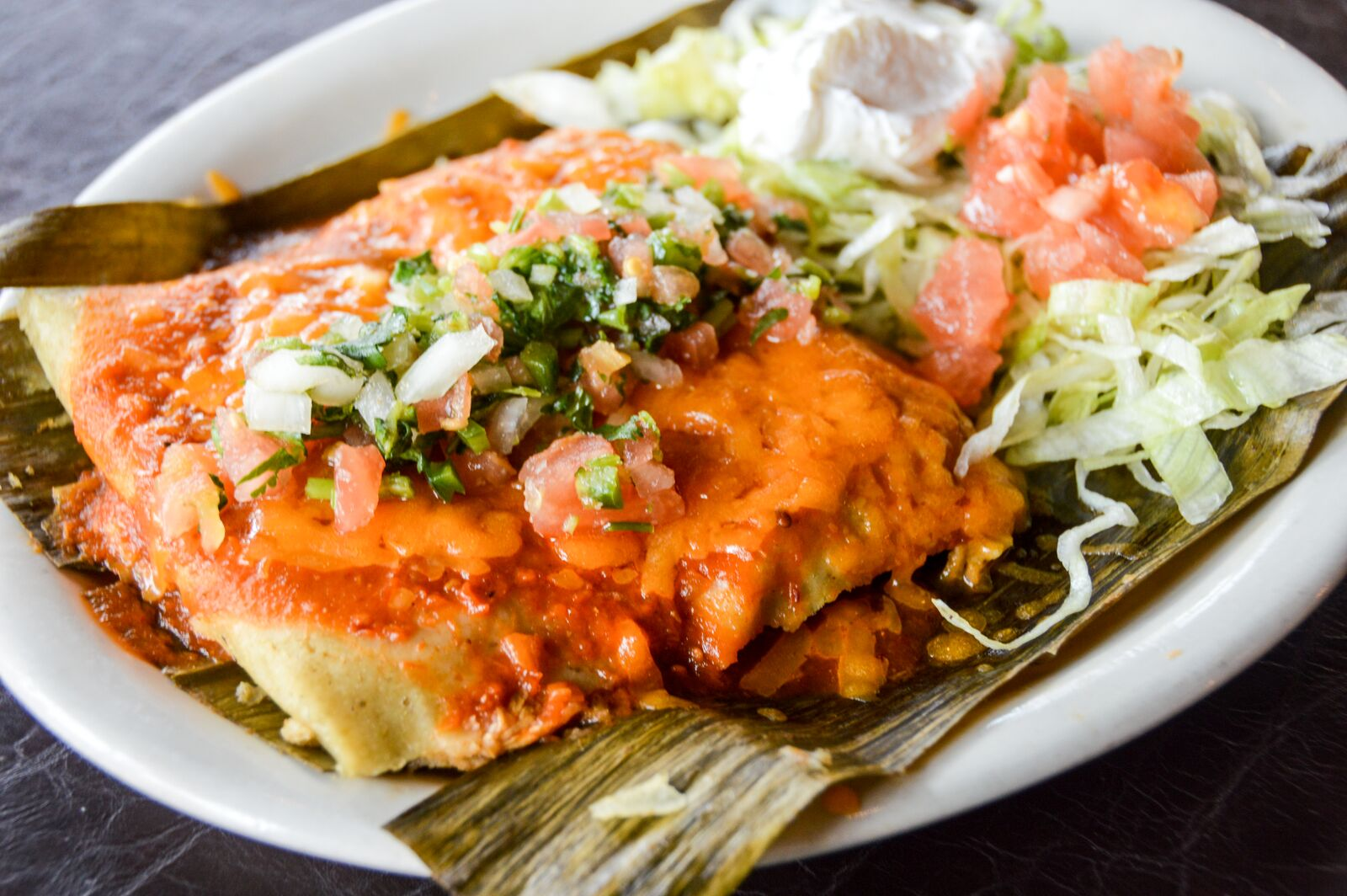 tamales with lettuce, sour cream and diced tomatoes