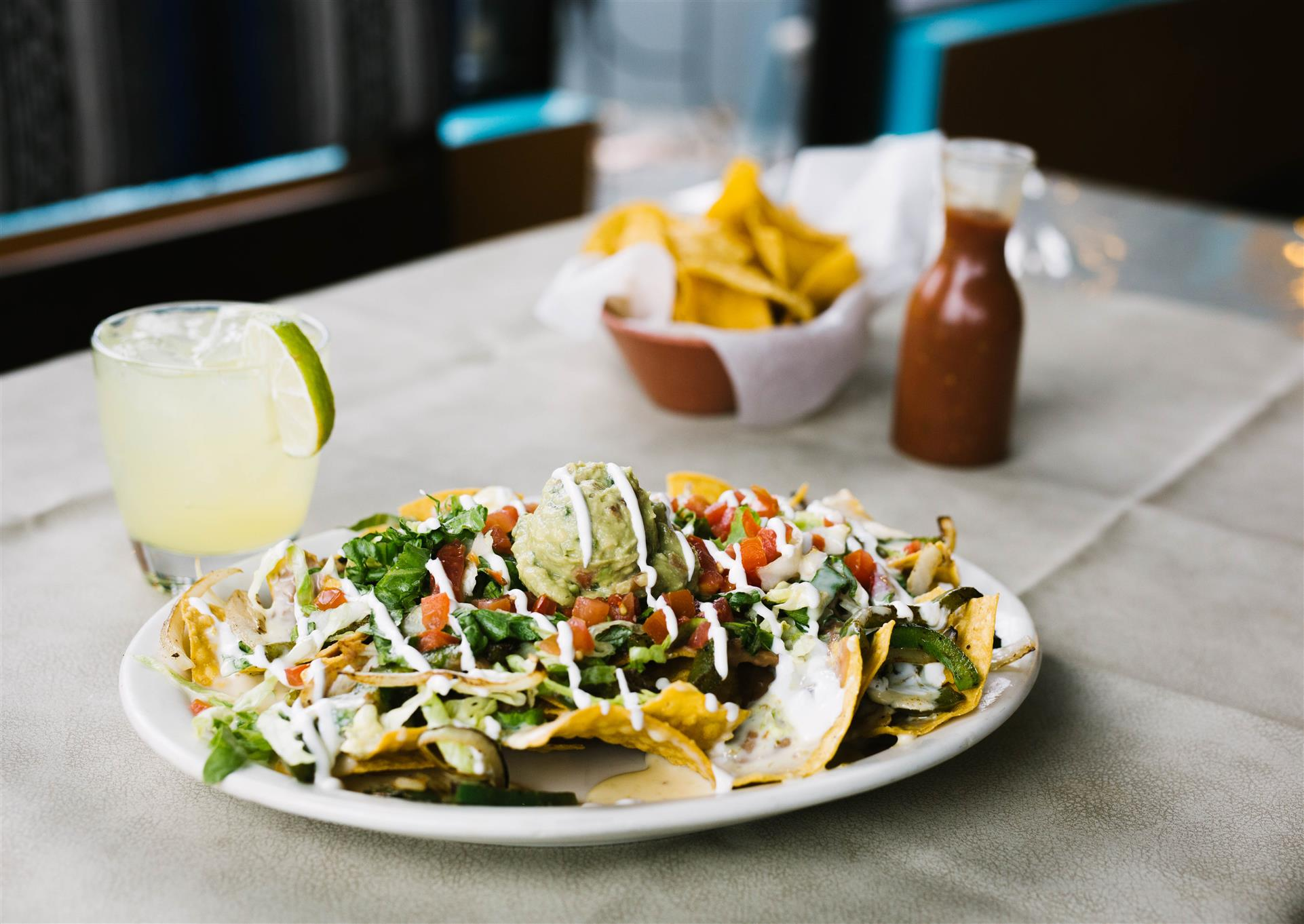 nachos with various toppings and side of margarita