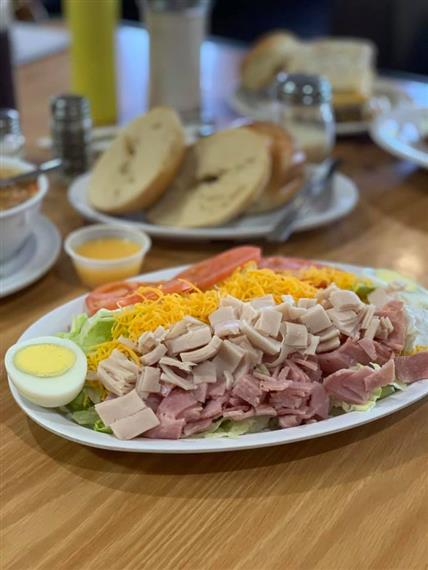 large salad with turkey, ham, cheese, egg, tomatoes and lettuce