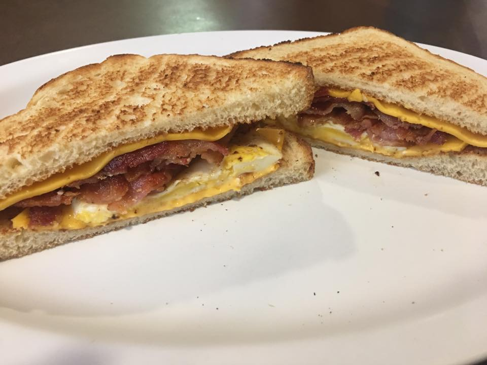 eggs, cheese and bacon on white toast