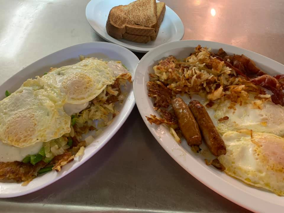 One plate with two Eggs over-easy over Country Fried Steak and homefries. Another plate with two eggs over easy, two sausage links, bacon and homefries. Plate of wheat toast.