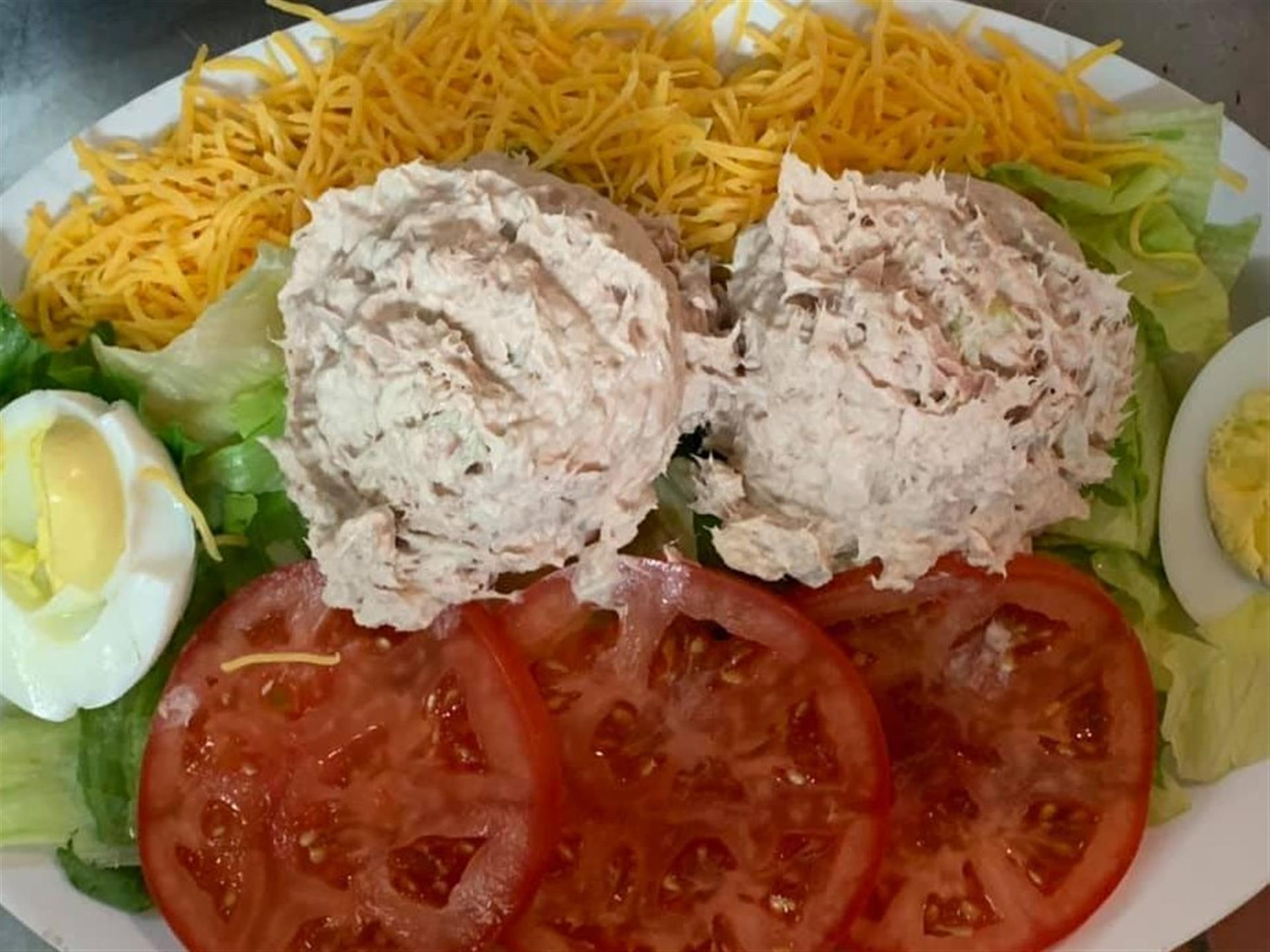 Cold Plate. Chicken and tuna salad scoop, tomato and boiled egg served on a bed of lettuce