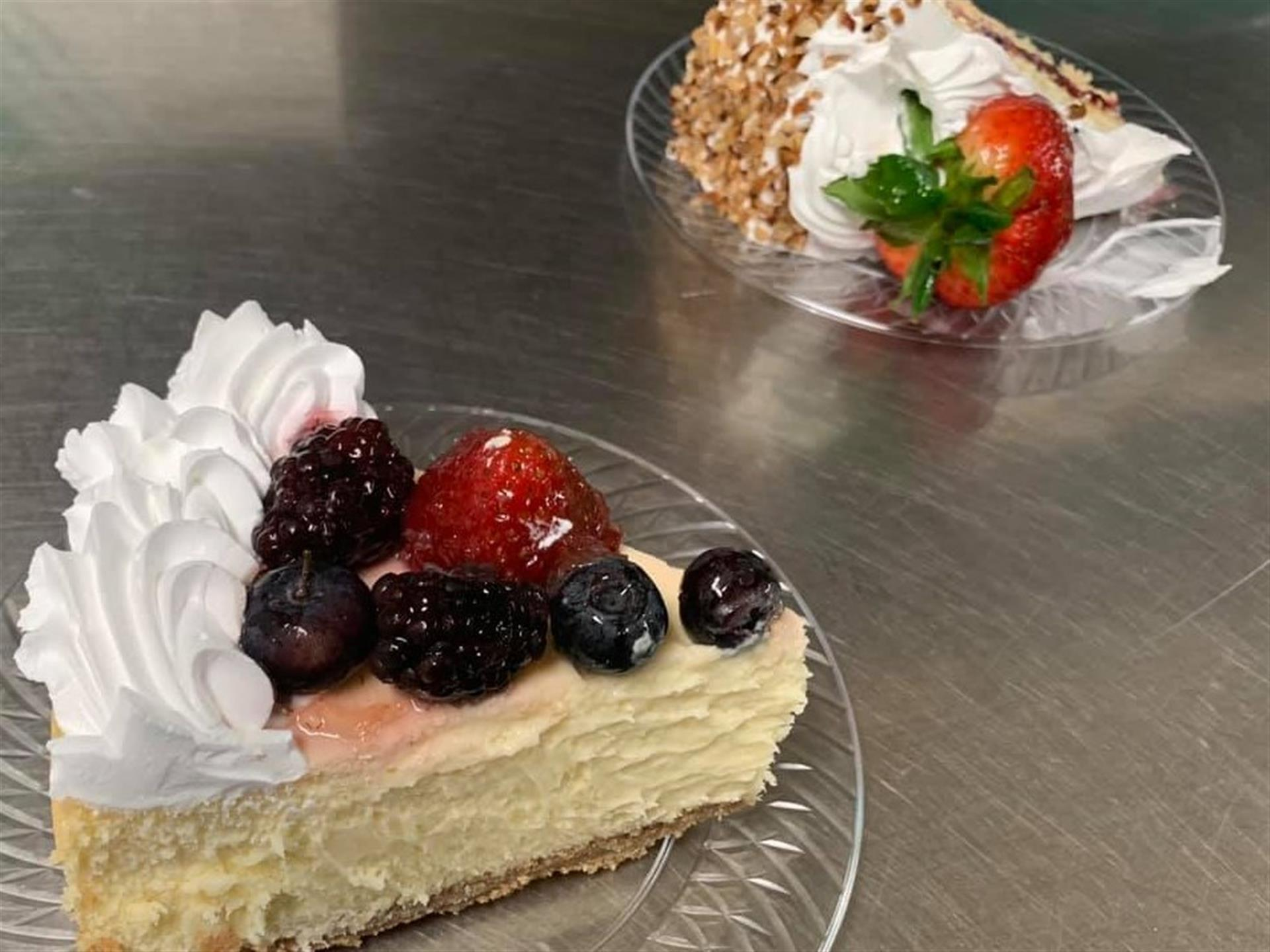 two cheesecake slices topped with fresh fruit.