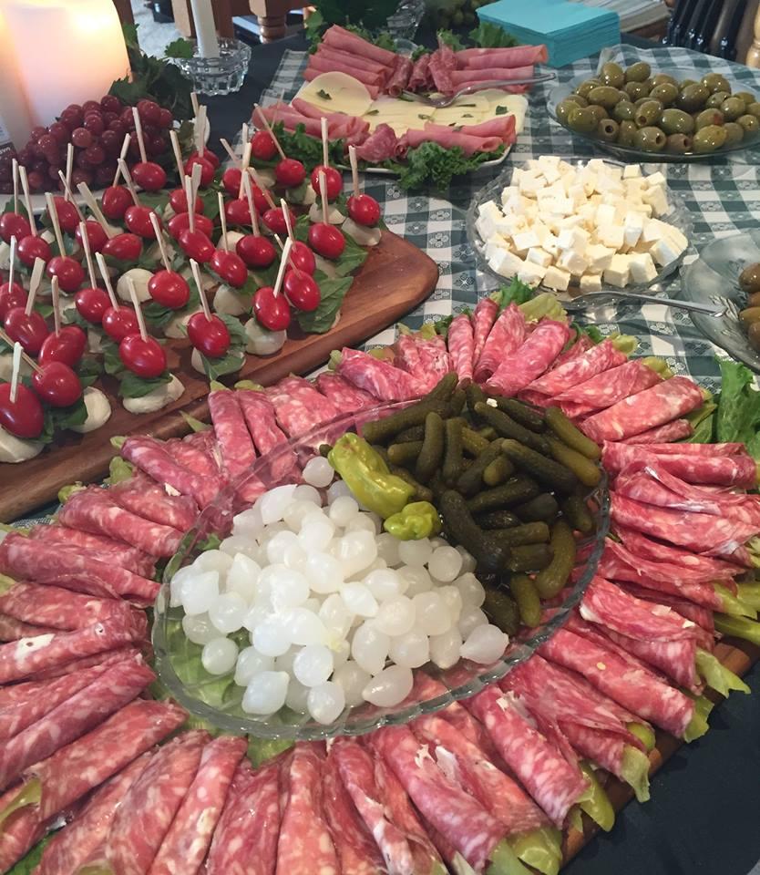 various appetizer plates with meats, skewers and vegetables