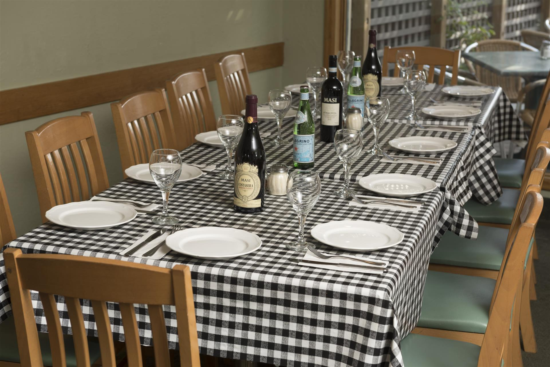 Table setting with plates, glasses, bottles with chairs
