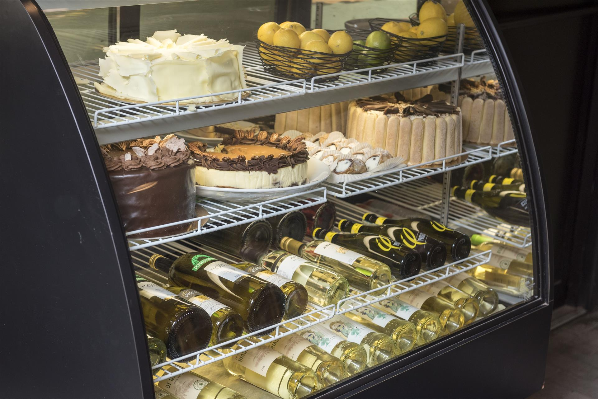 Assortment of Desserts and Wine stored in a fridge