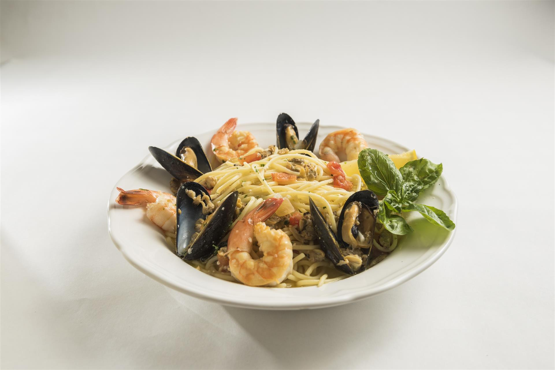 Mussels, prawns & clams with tomato, onion, lemon butter basil white  wine topped over spaghetti