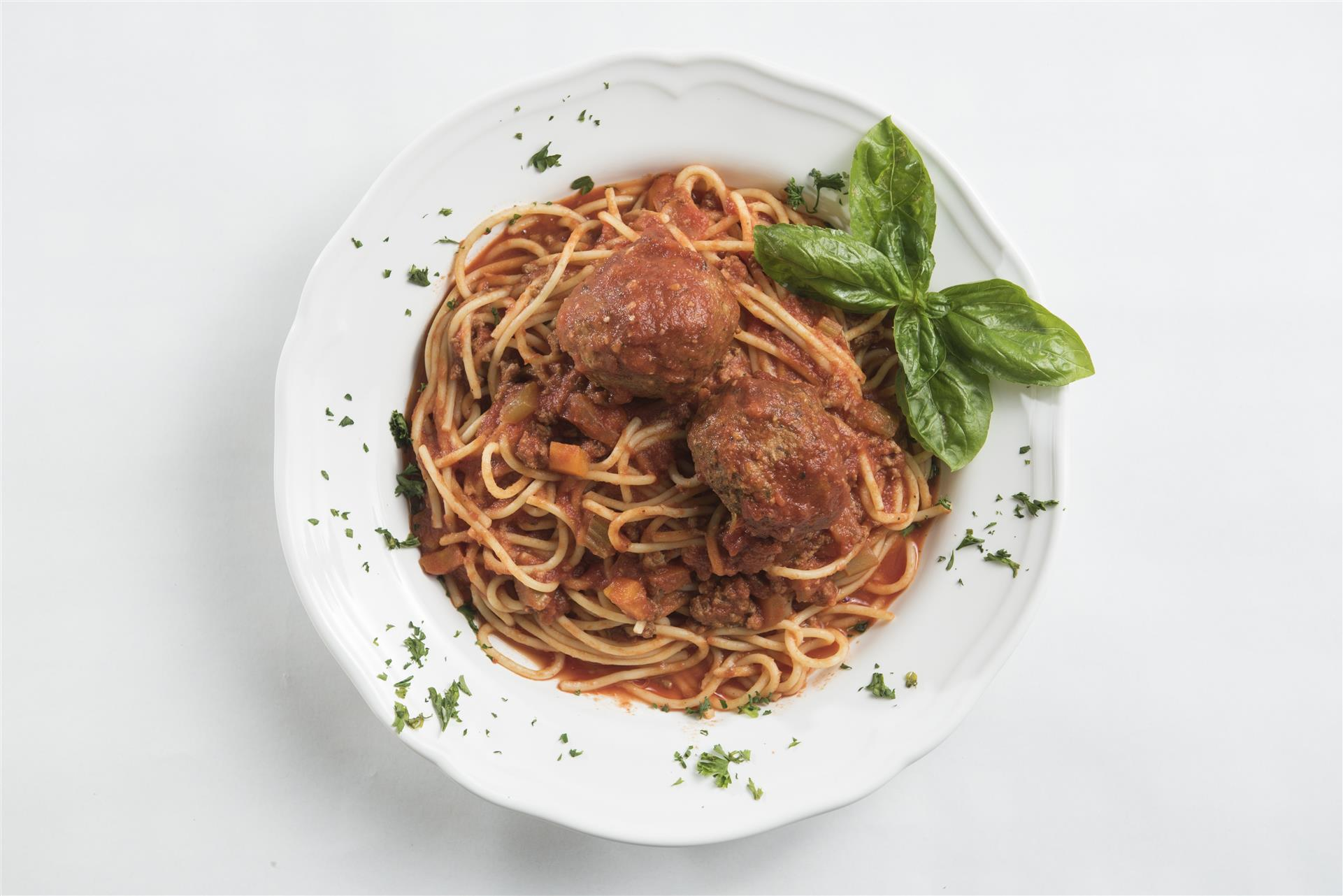 spaghetti with two meatballs topped with fresh basil in a bowl