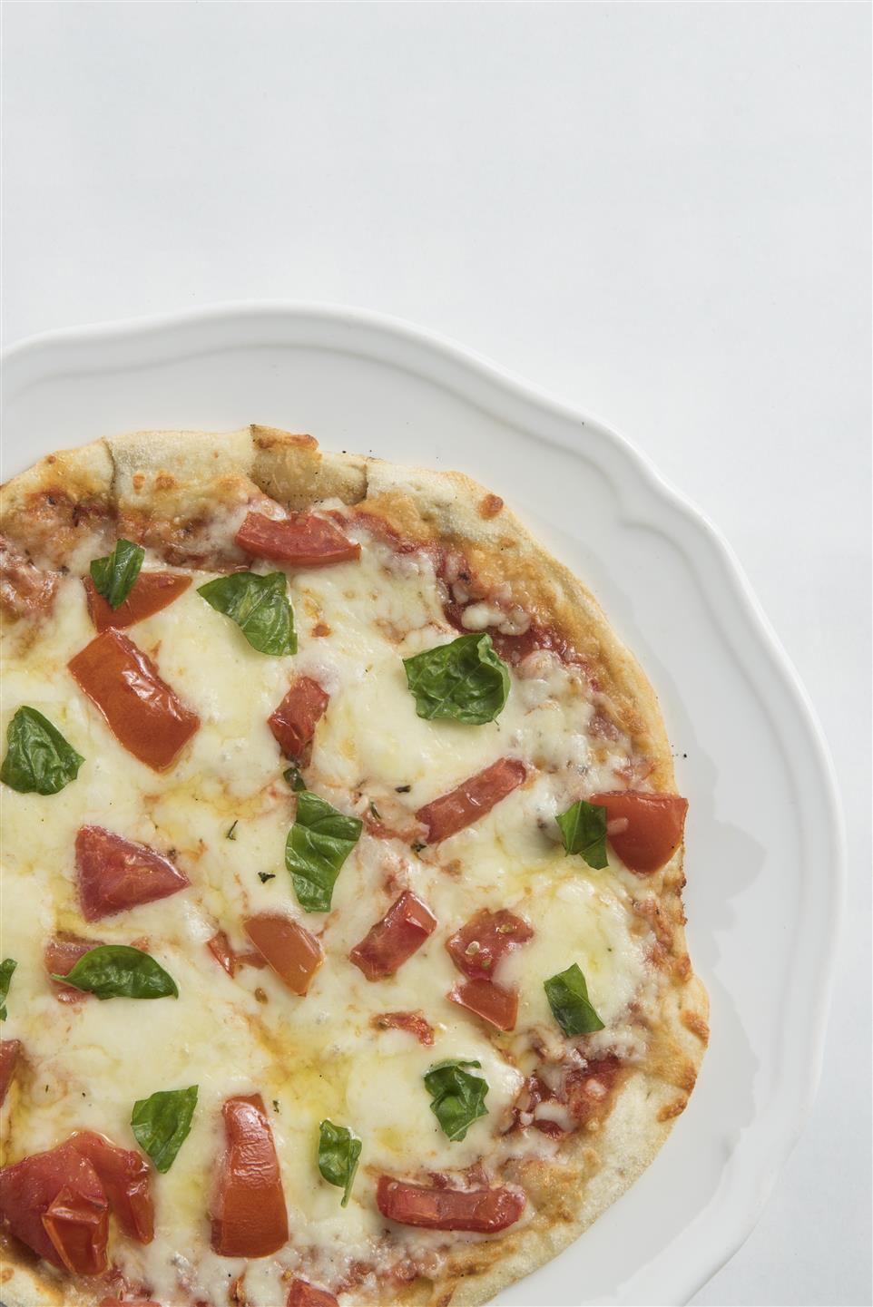Cheese pizza topped with tomtoes and fresh basil