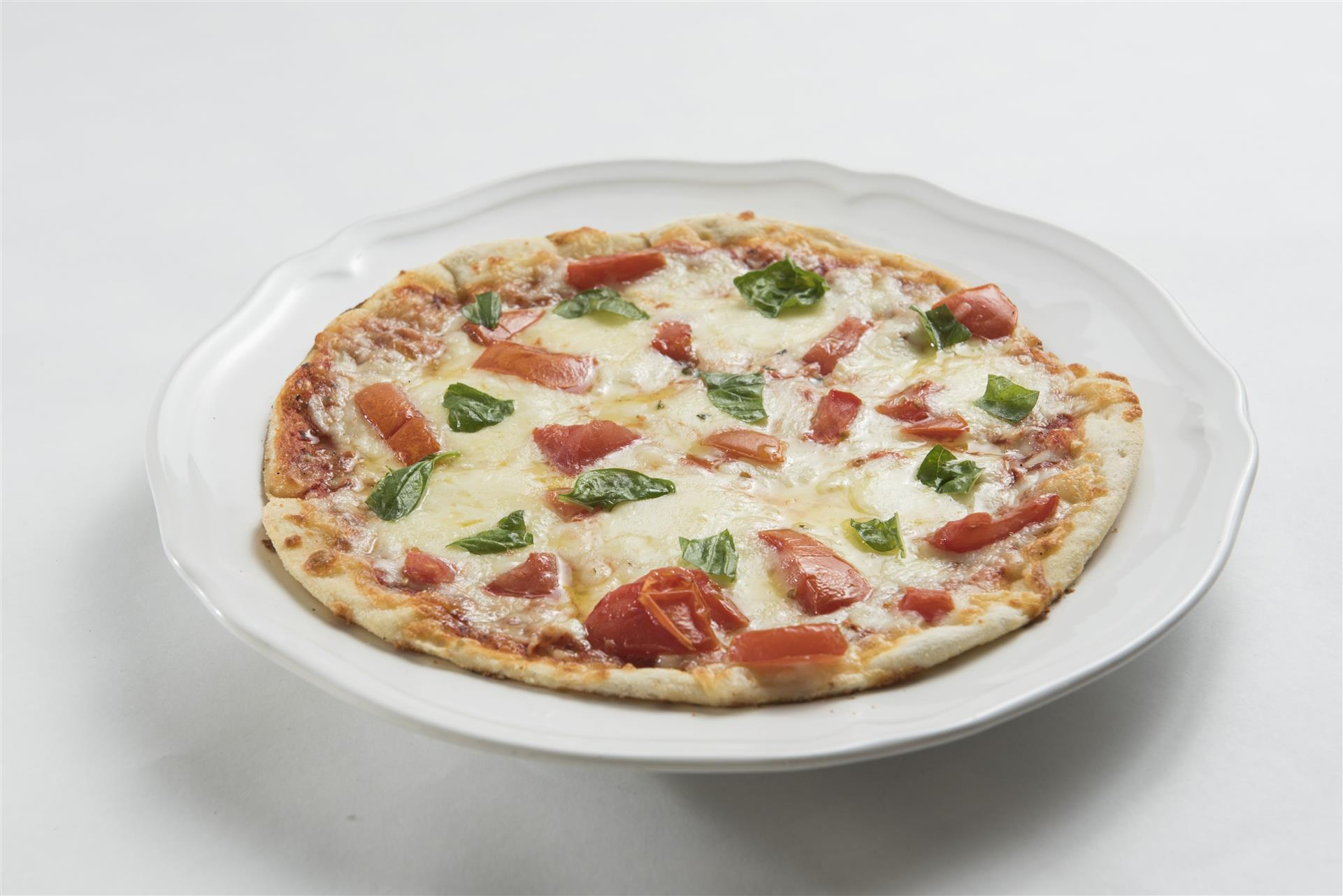 Cheese pizza topped with tomatoes and fresh basil