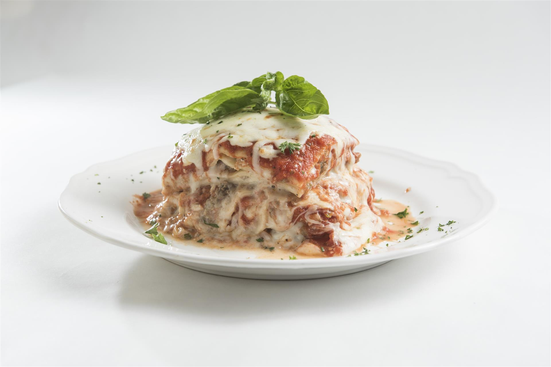 Lasagna topped with fresh basil on a plate