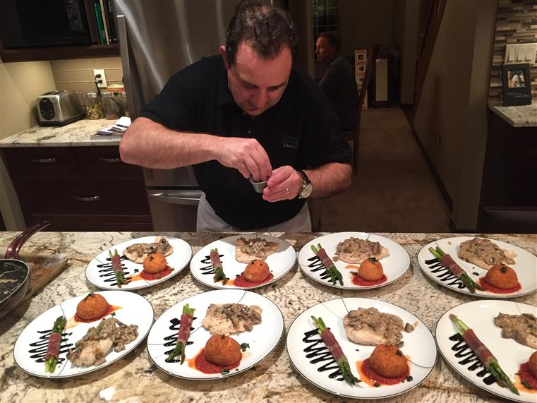 Chef garnishing plates of food for catering