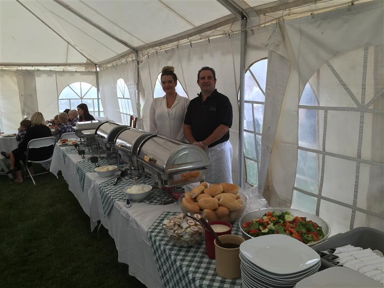 two people standing behind a catering table in a tent