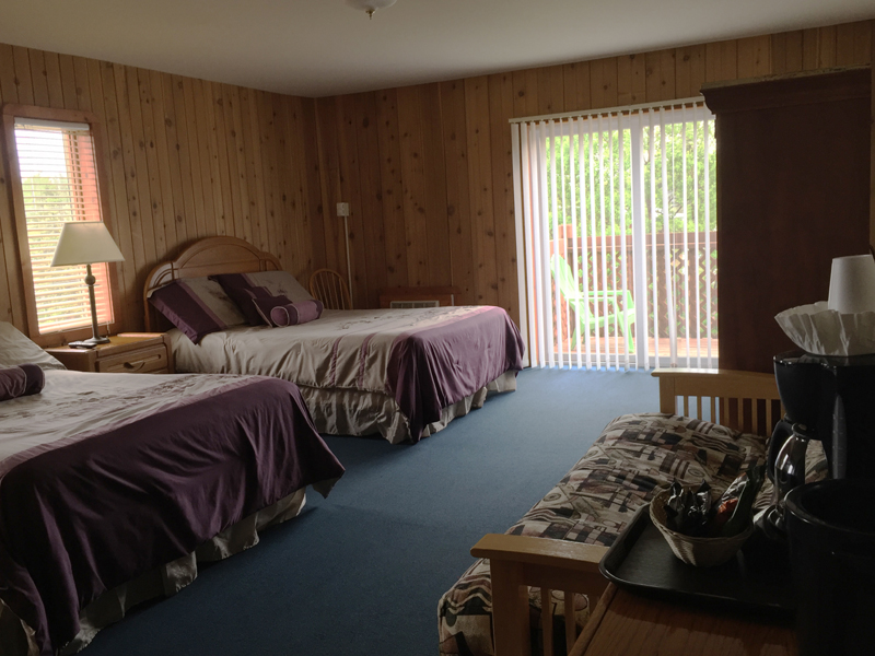 Motel bedroom showing couch, two beds and sliding door out to balcony