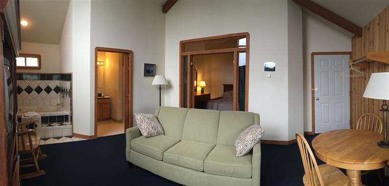 Honeymoon suite showing couch, bedroom, closets, table and chairs.