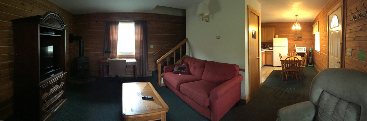 Living room area with couch, table, window and stairs leading up