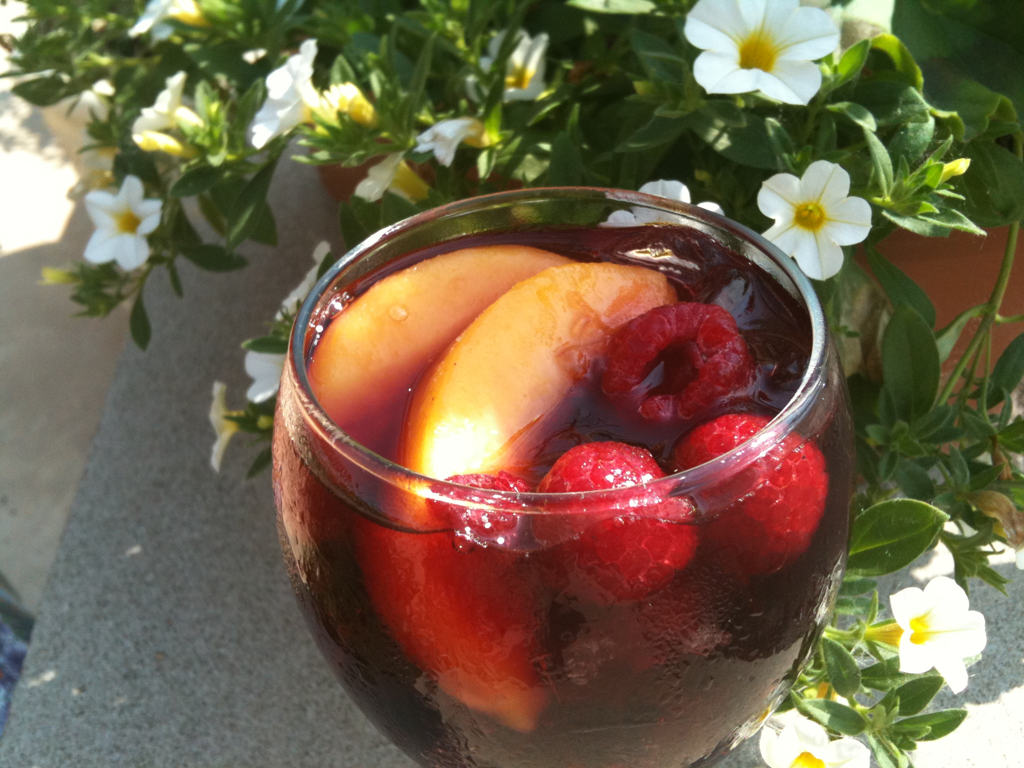 Sangria in a glass with peach slices and raspberries