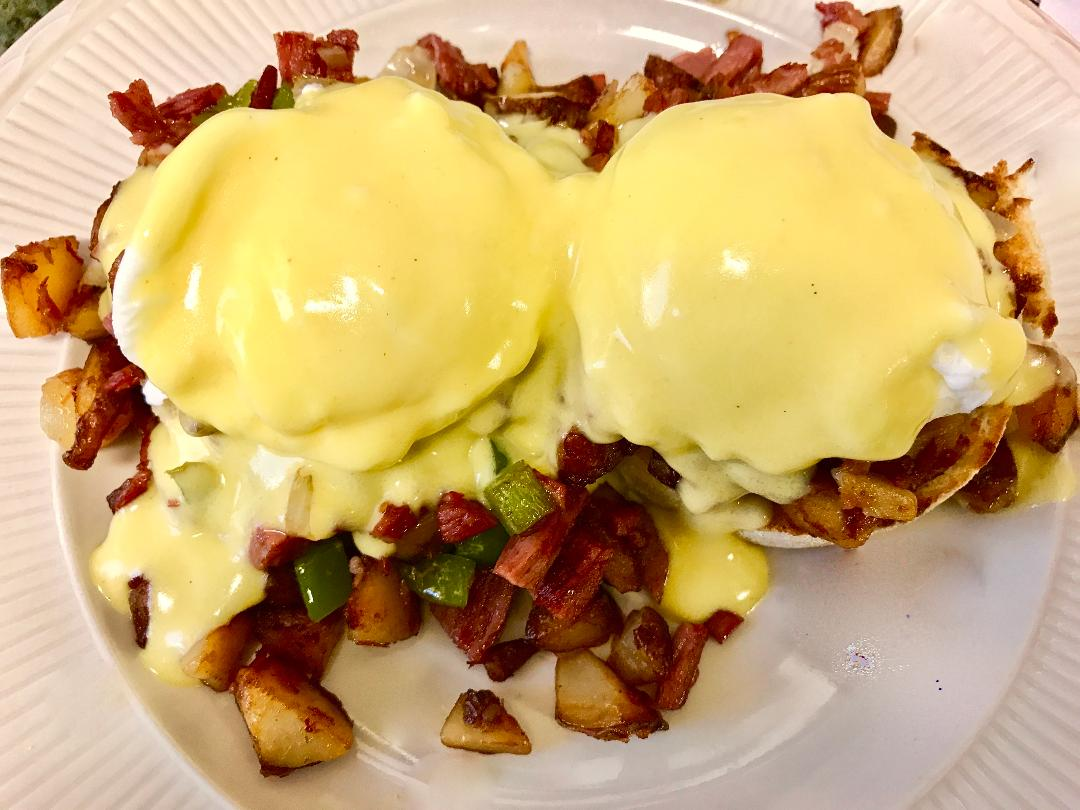Eggs benedict over breakfast potatoes with peppers and onions