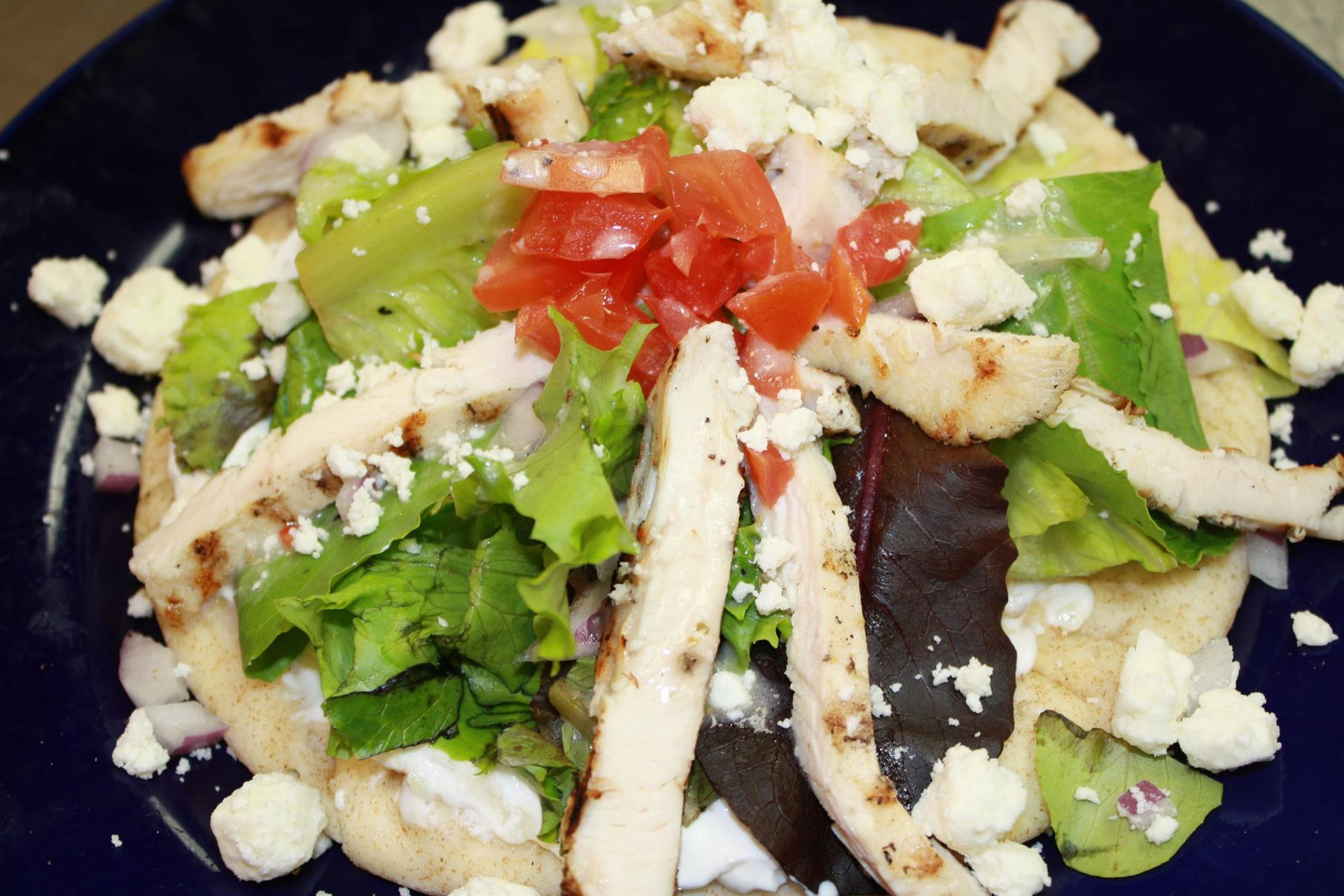 a salad with grilled chicken, feta cheese, and tomato