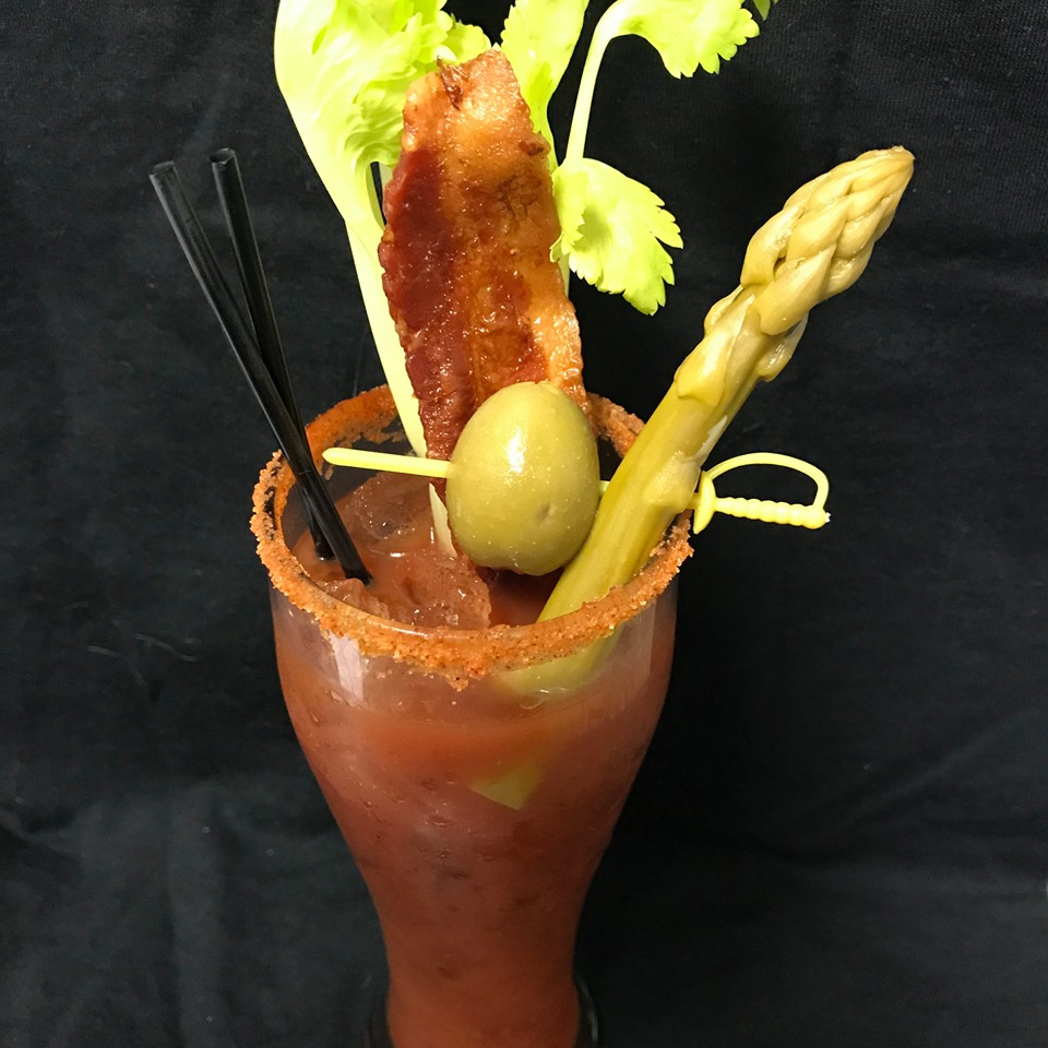 a bloody mary with asparagus, celery, bacon, and green olive