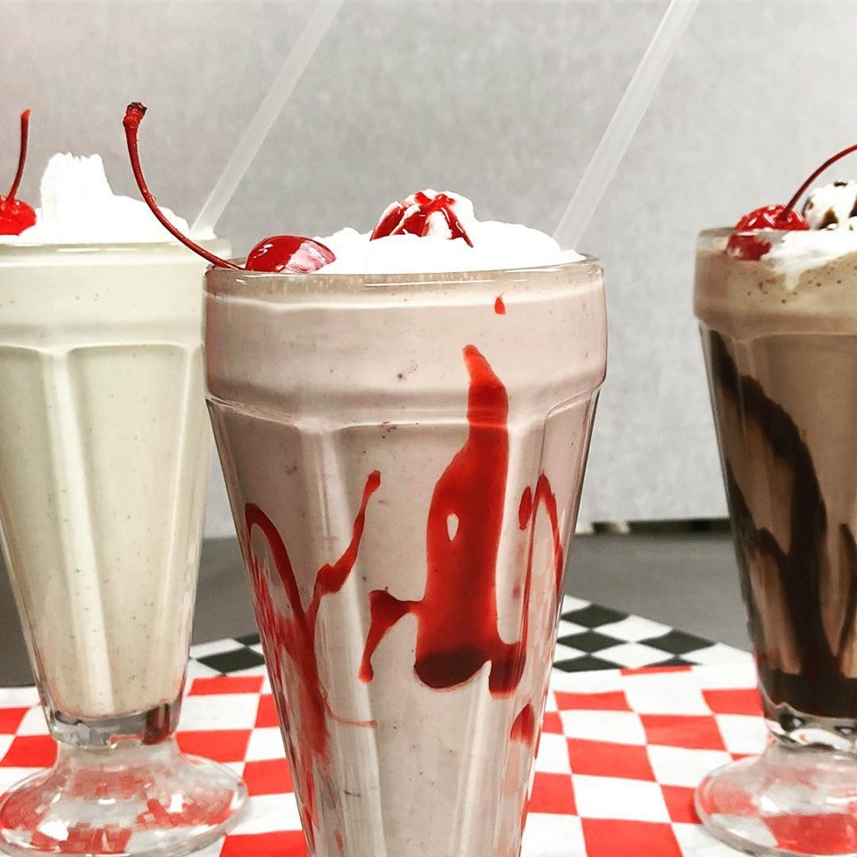 a vanilla, strawberry, and chocolate milkshake on a checkered table