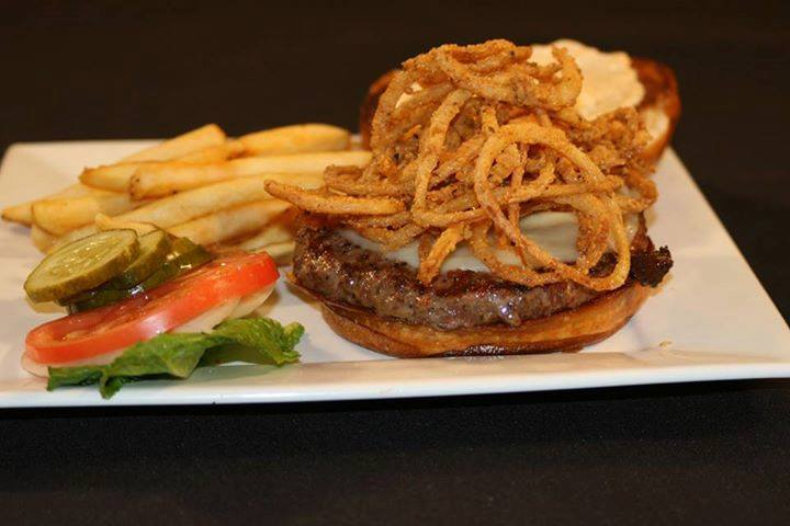 an open faced burger with onion straws and a side of french fries