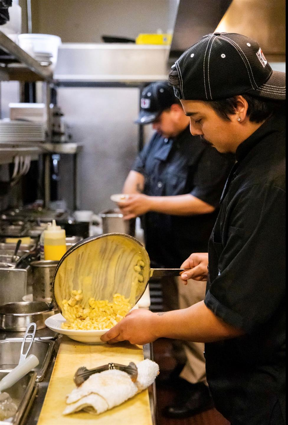 a chef pouring the mac and cheese from the pan onto the plate