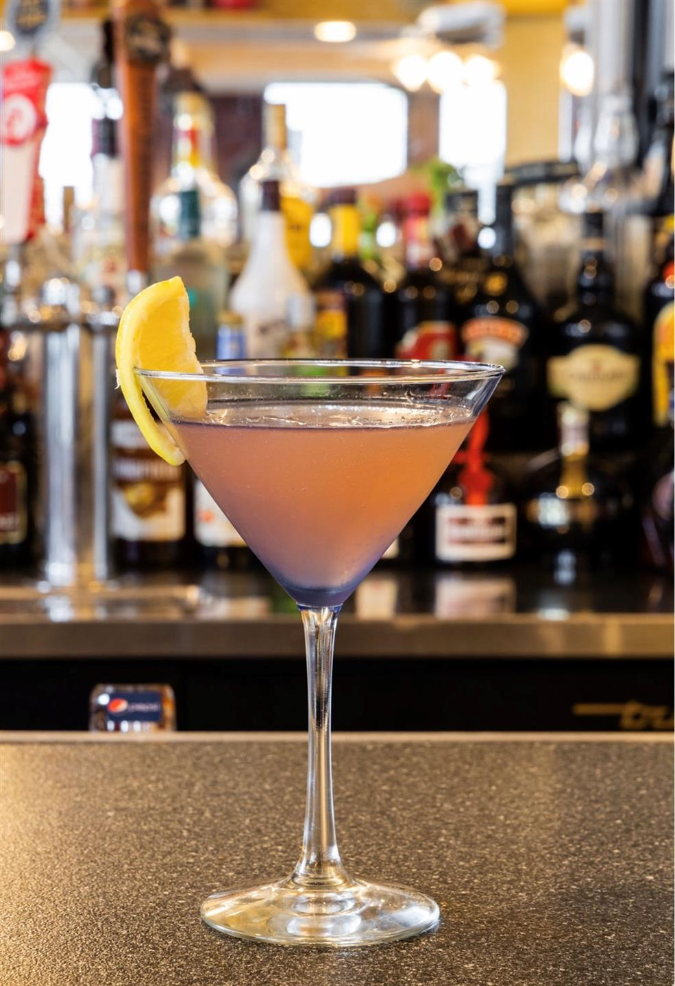 a pink martini on the bar with a lemon wedge