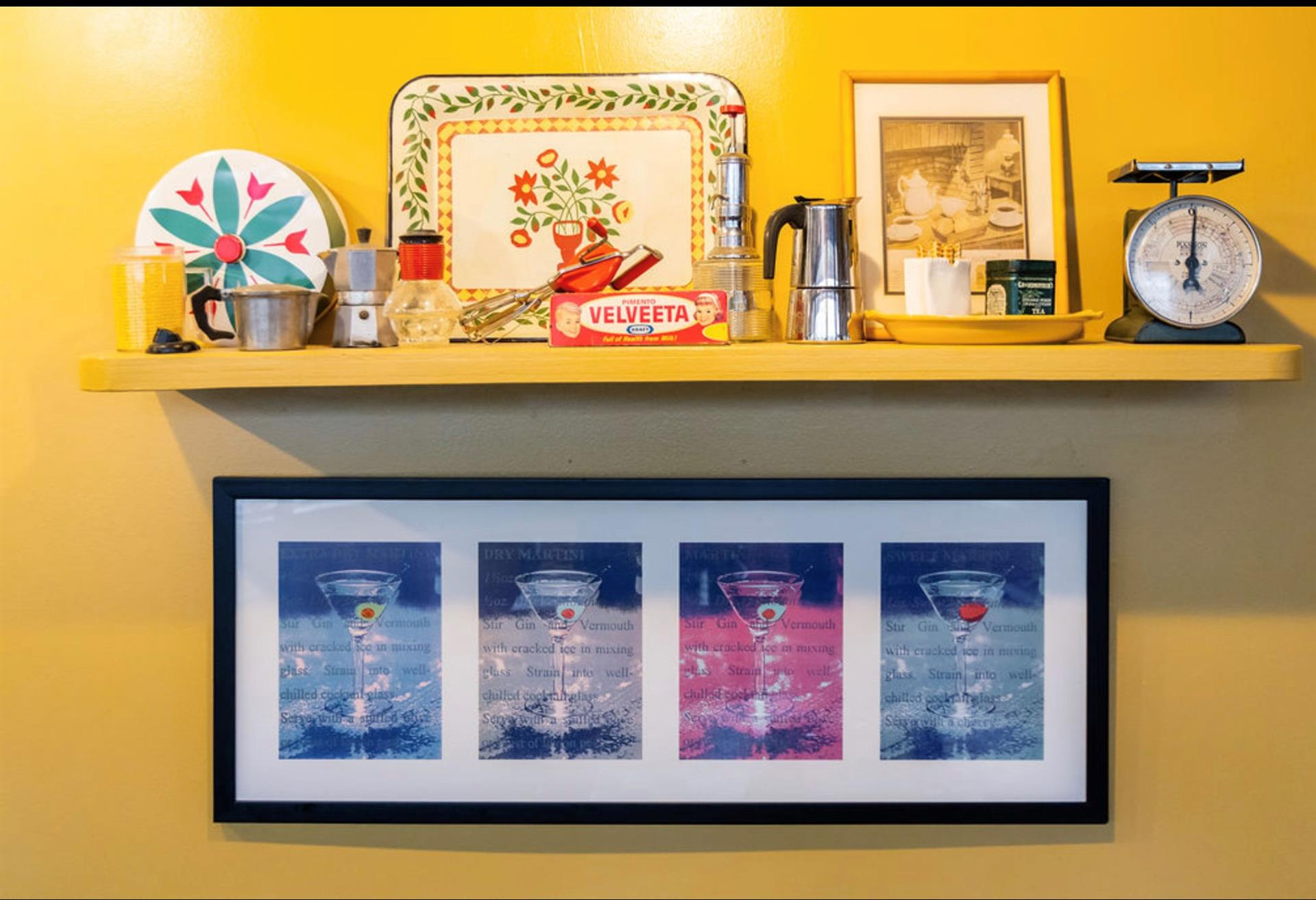 a shelf with decorative plates, an espresso machine and a picture frame of different colored martini glasses