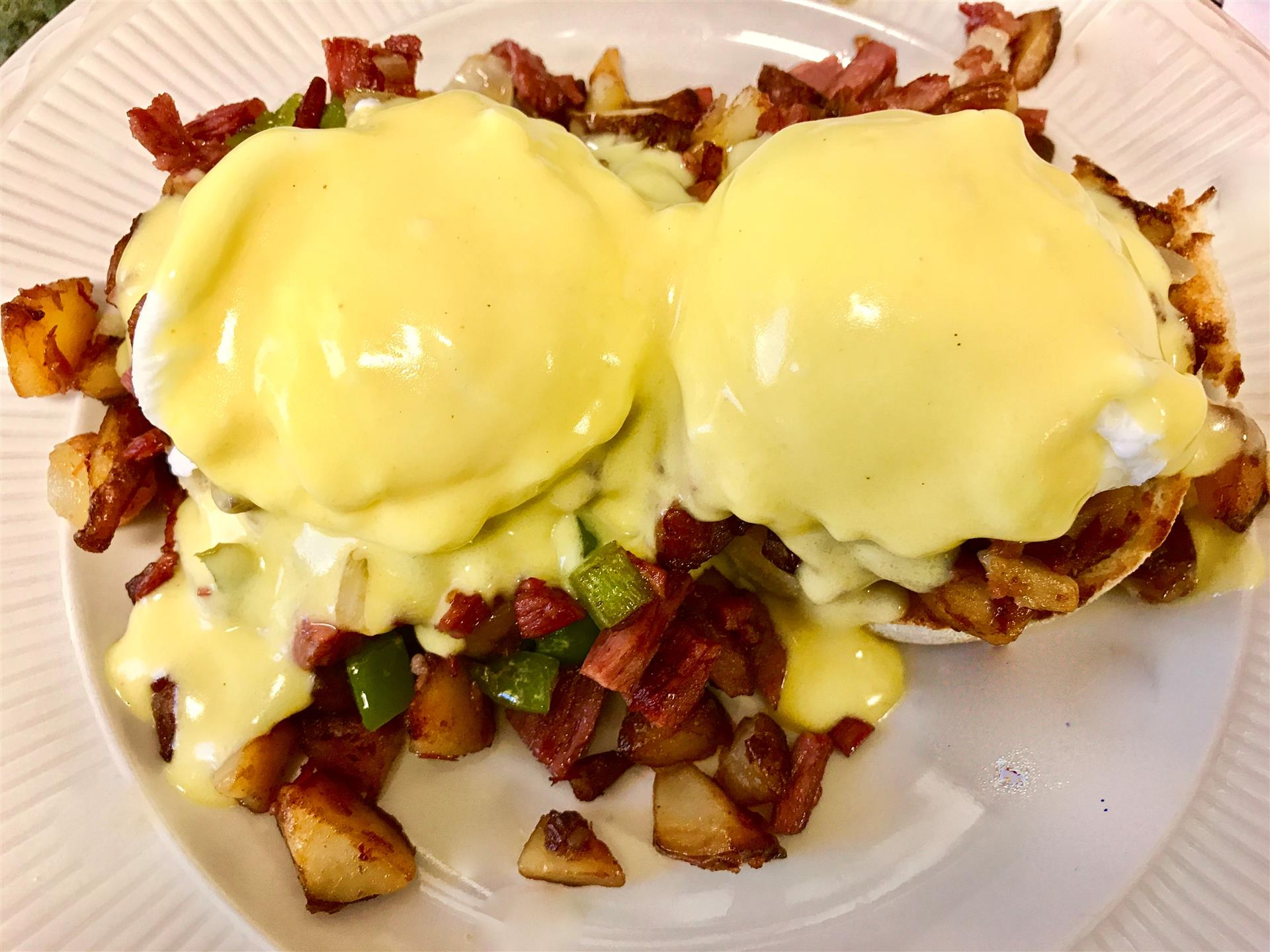 eggs benedict with a side of potatoes