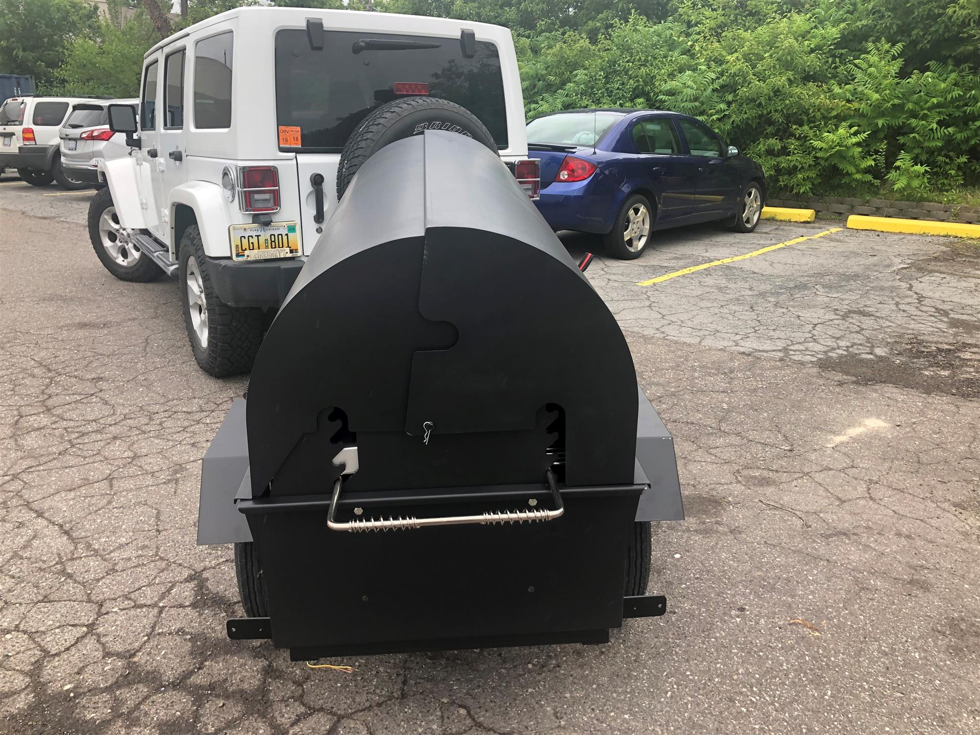 grill hooked up to the back of a white jeep