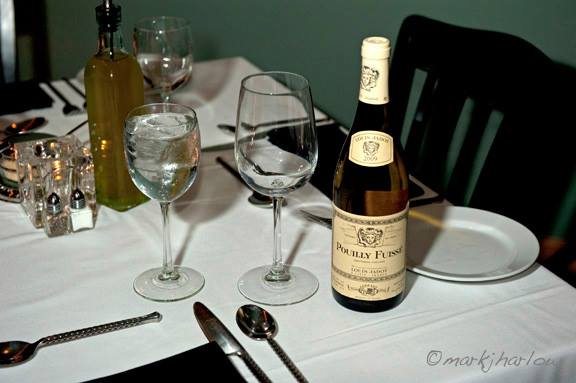 wine bottle and glass next to placesetting on white-clothed table