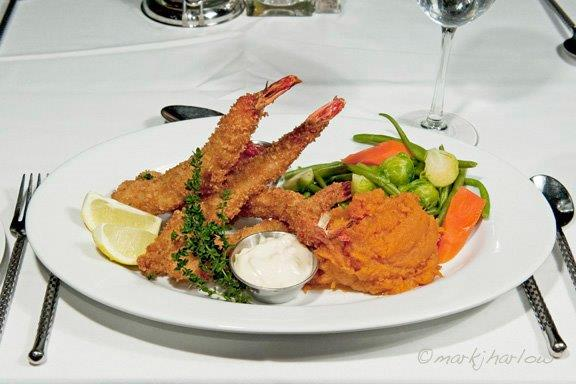 Golden Fried Prawns. Hand breaded jumbo shrimp, fried and served with cocktail and tartar sauce, house vegetable and mashed sweet potatoes.