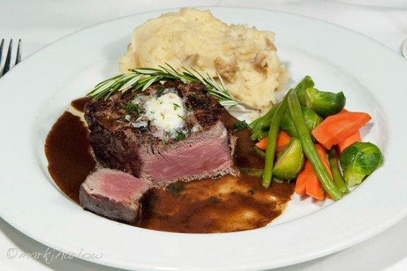 Filet Mignon. Broiled 7 oz. filet mignon with port wine demi-glace and hotel butter, house vegetable and mashed potatoes