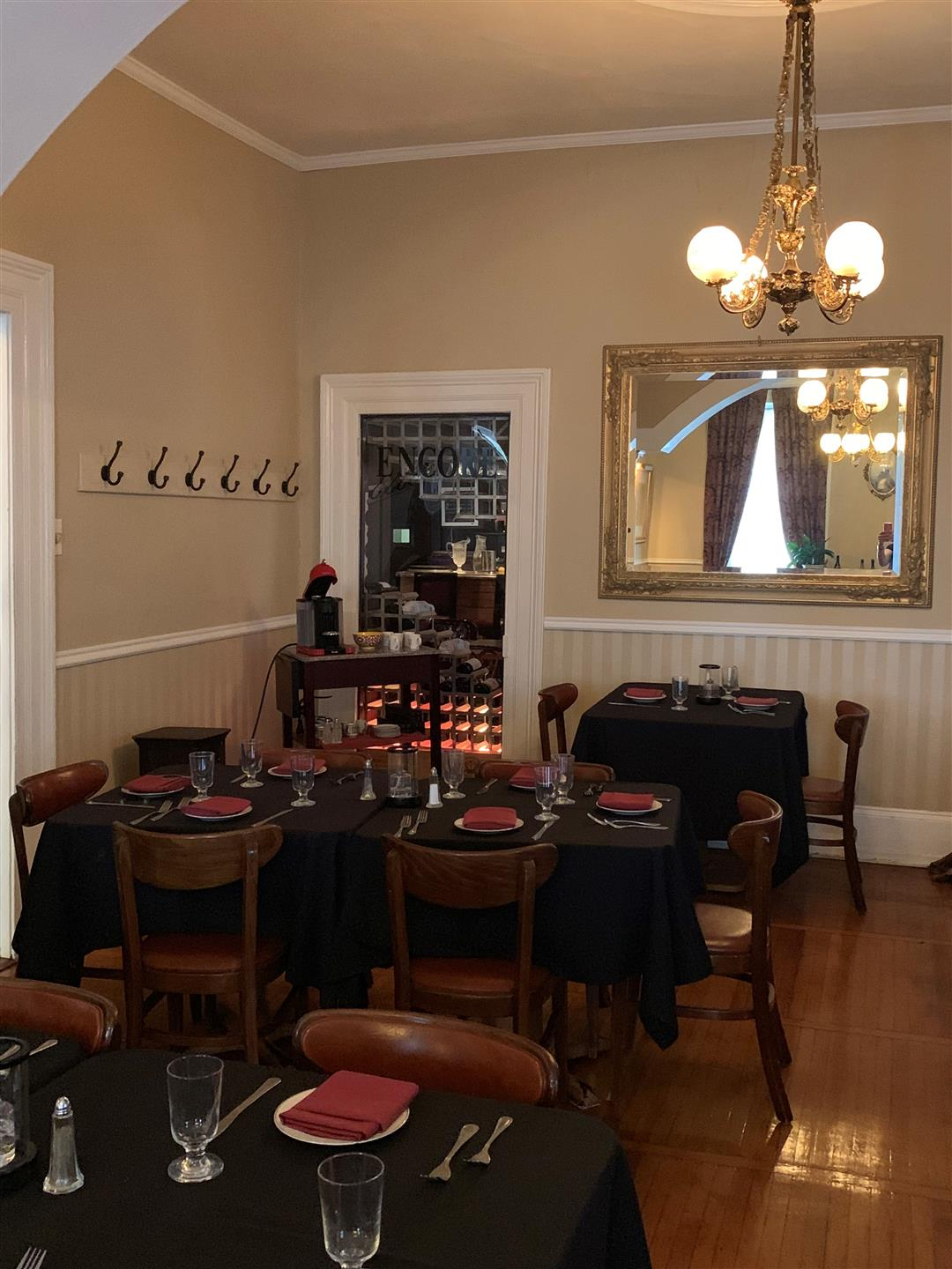 dining room filled with set tables and chairs with coat hooks hanging, mirror on the wall and Chandeliers hanging
