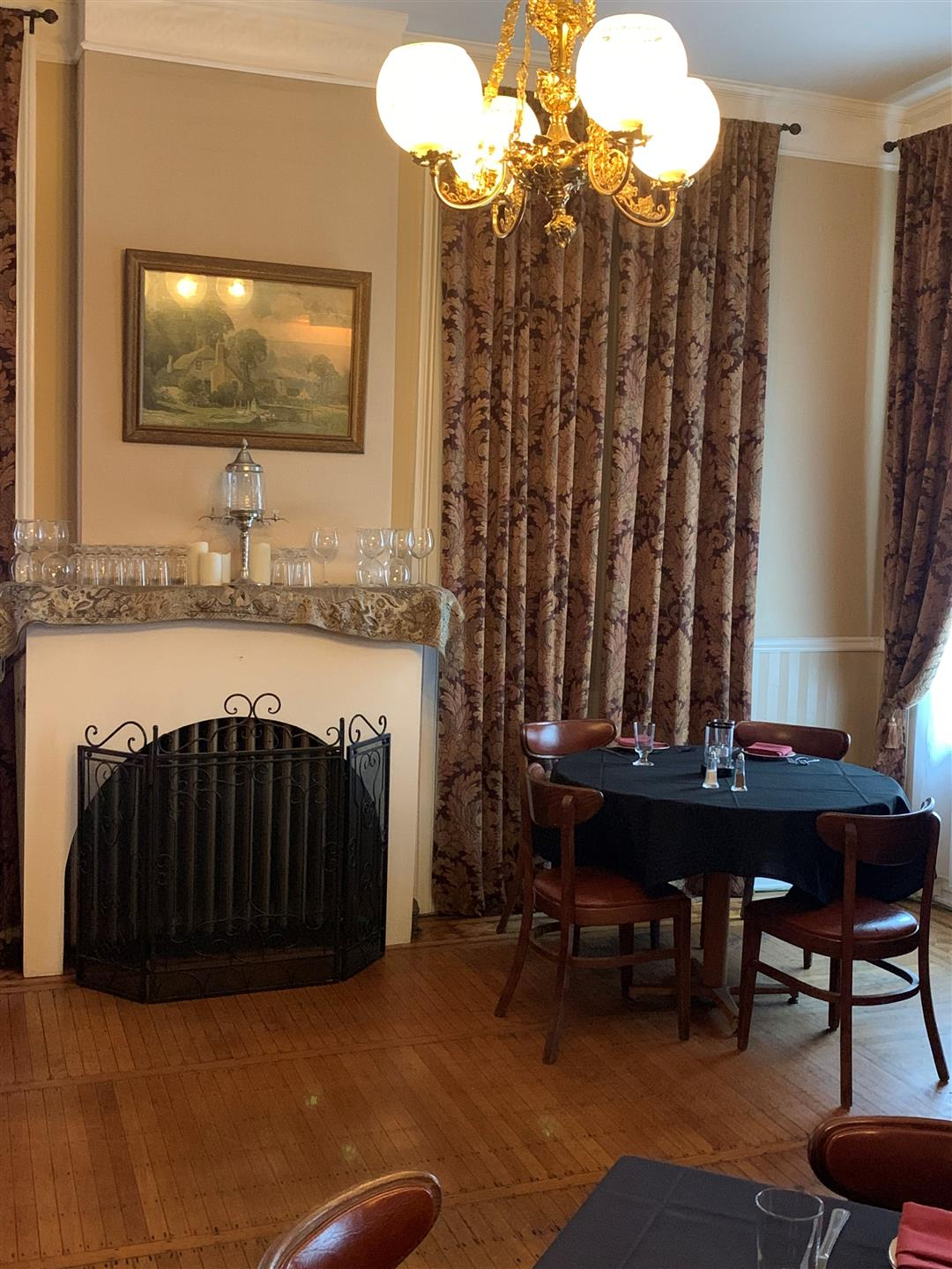 dining room filled with set tables and chairs with a fire place and curtains hanging over the window