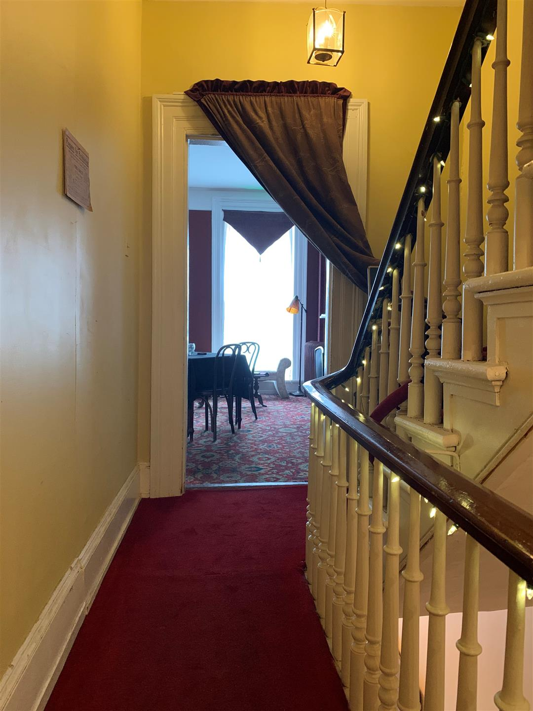 Hall way leading up to dining room with stair case on the righthand side