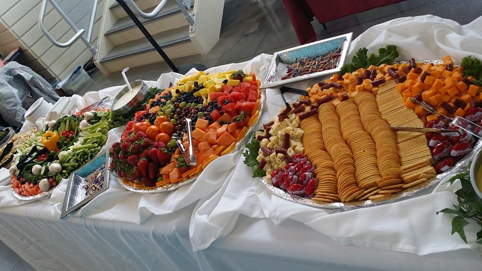 Catering trays with assorted fresh cut fruits, cheese and crackers on a table
