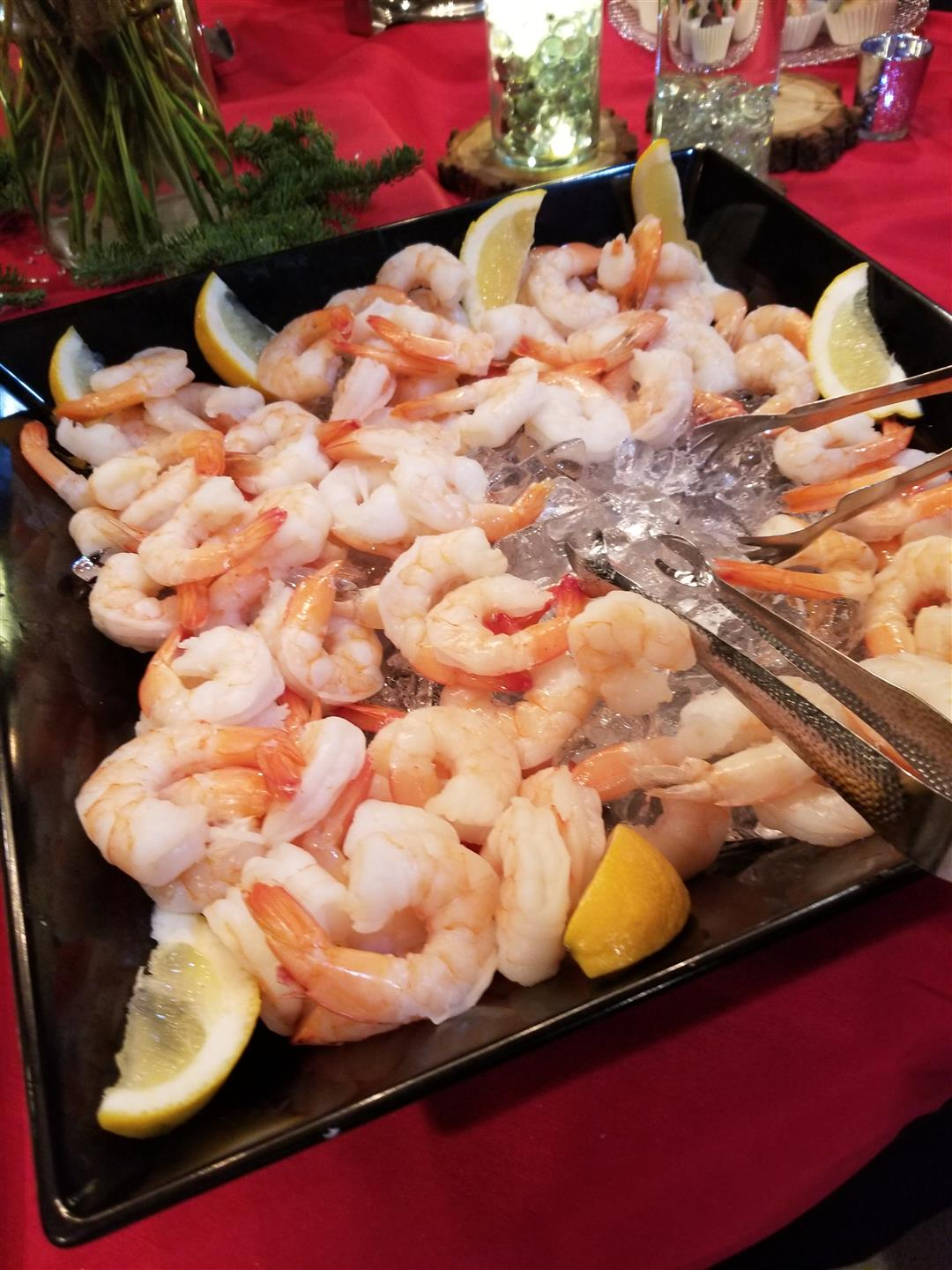 Assortment of Shrimp in a tray with sliced lemons with two tongs