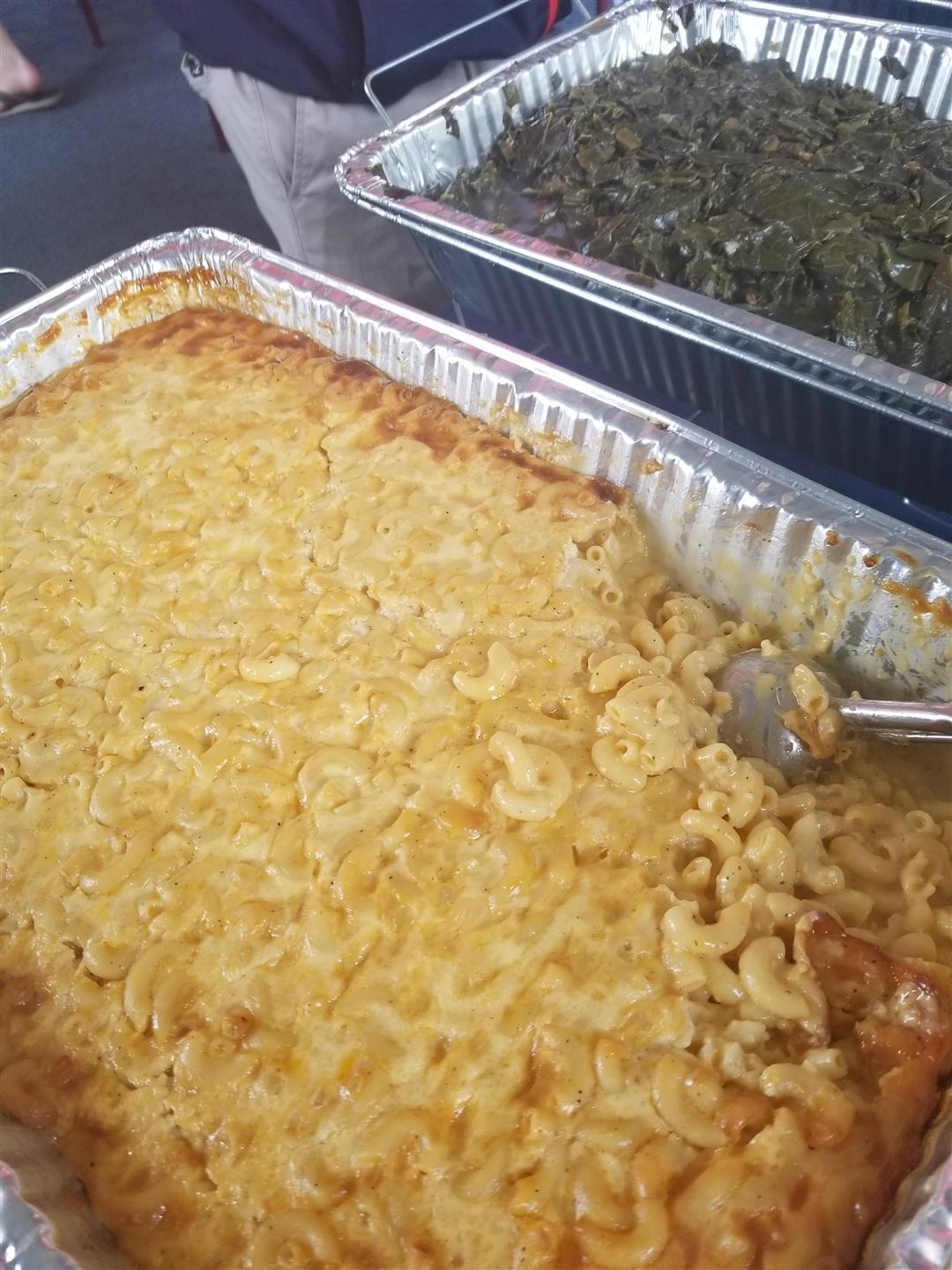 Mac and Cheese in a tray with a serving spoon in it
