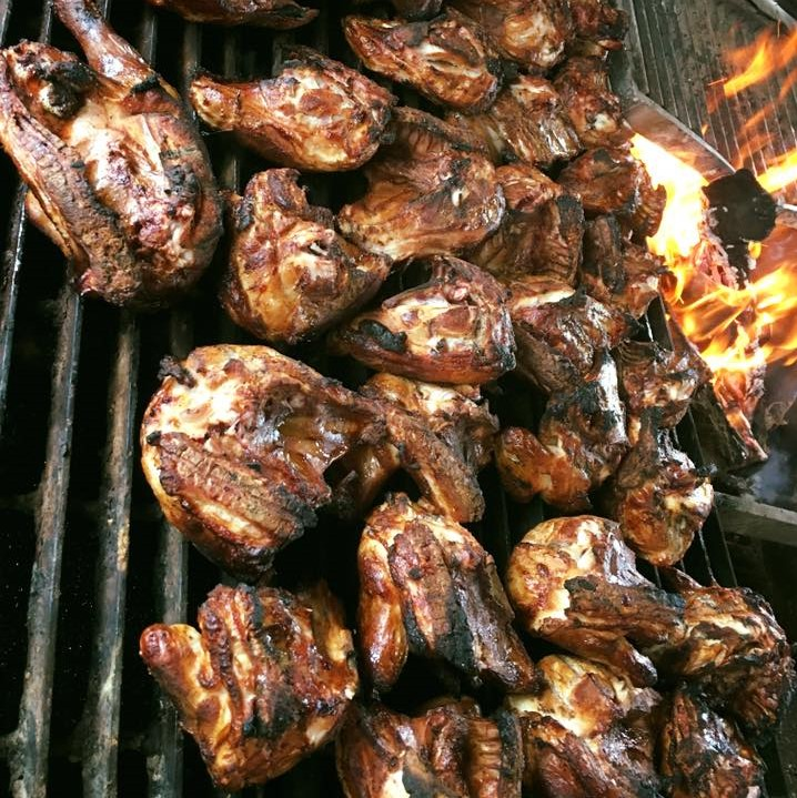Multiple grilled chicken breasts on a grill