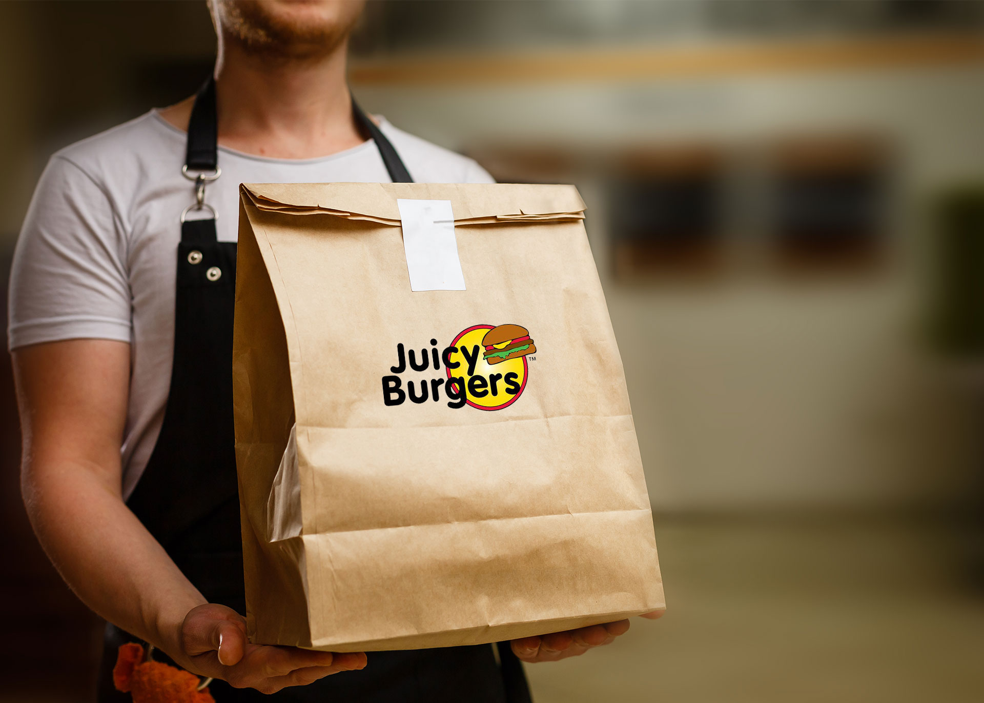 Server holding a brown paper bag with Juicy Burgers branding